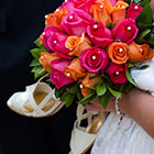 Bride holding her shoes and bouquet